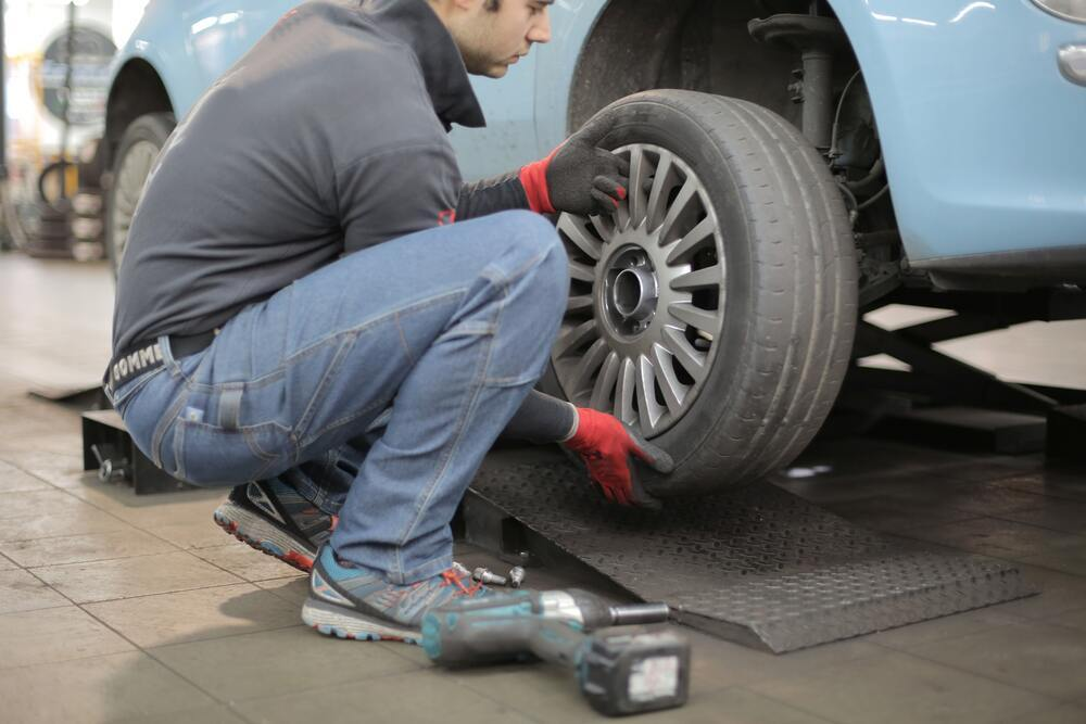 Man removing tyre to check brakes